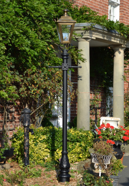 Antique brass lamp post in flower bed
