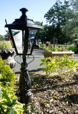 Pillar light in garden flower bed