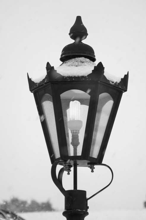 Lantern with snow covered top black and white